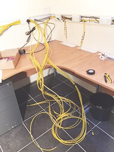 an onsite set up of internal cabling. The image shows a desk and yellow wires