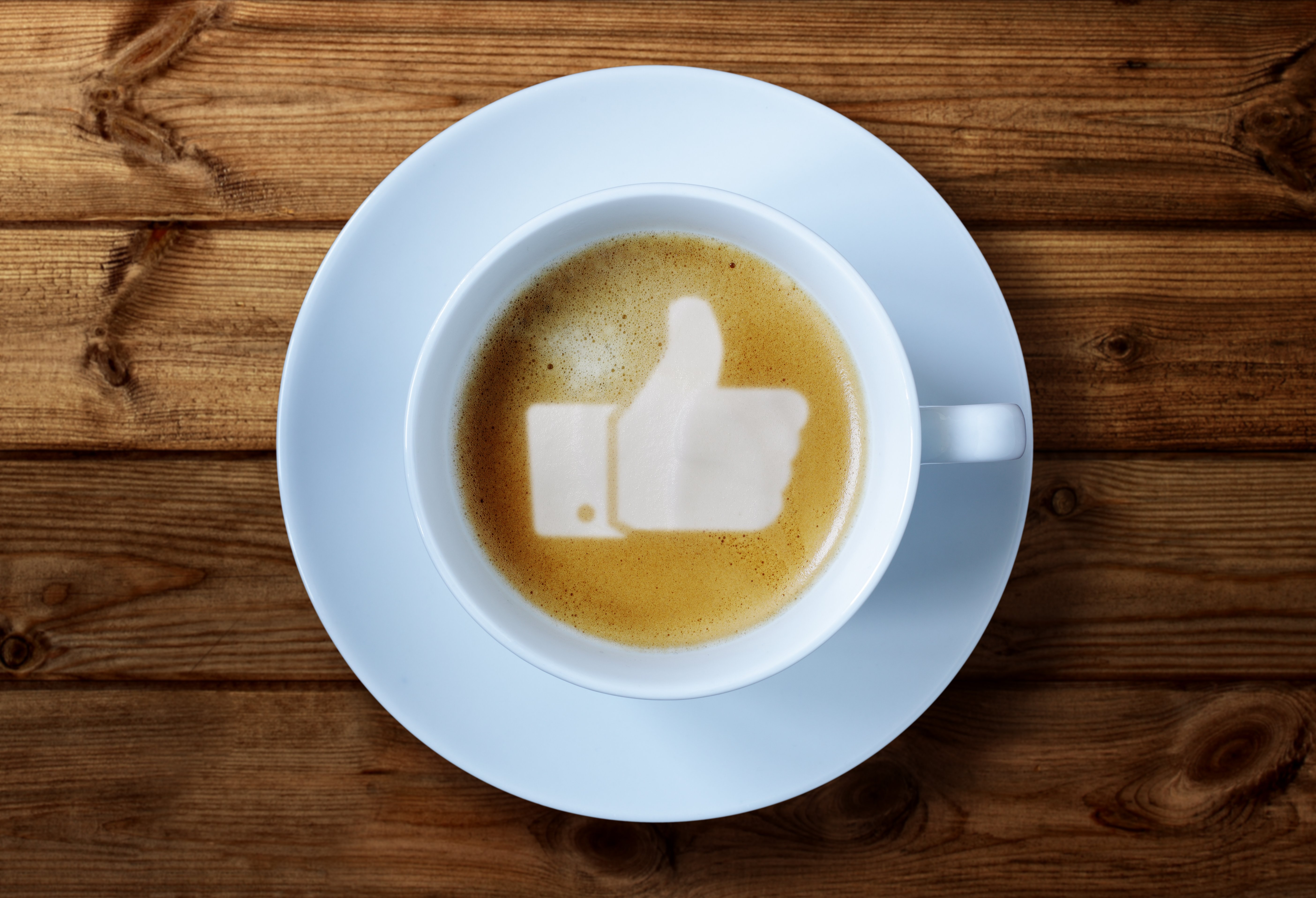 Thumbs up or like symbol in coffee froth on a wooden table background