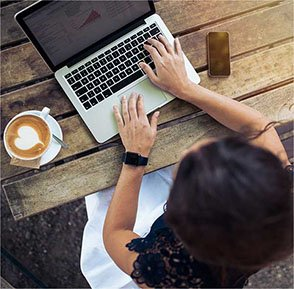 A lady outdoors working on her laptop on a wooden bench with her phone and coffee