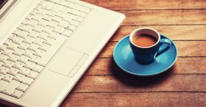 A cup of coffee on a wooden table beside a laptop