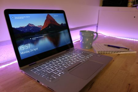 The HP Spectre x360 on a desk with mug and notepad
